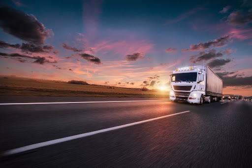 A truck driving on the road and facing truck driver turnover rate.